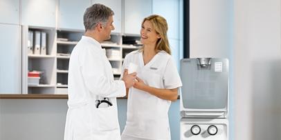 Arzt und Schwester erfrischen sich mit einem Glas frischem Wasser
